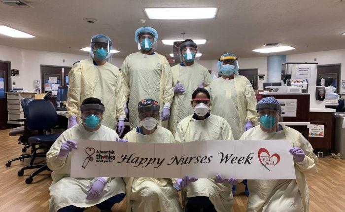 front line nurses smile together wearing ppe