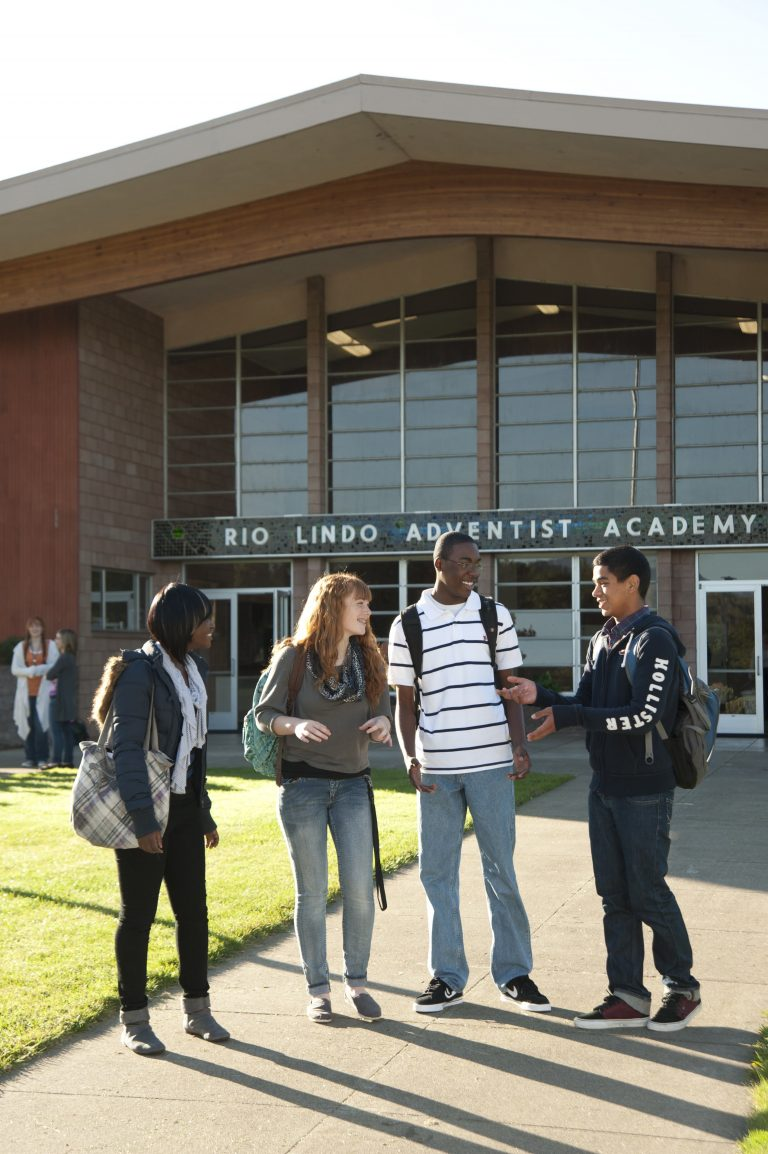 four students greet each other in front of the school